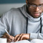 Closeup smart millennial african student wear glasses hold pen noting writing down information study use book preparing for university or college test exam, horizontal photo banner for website header
